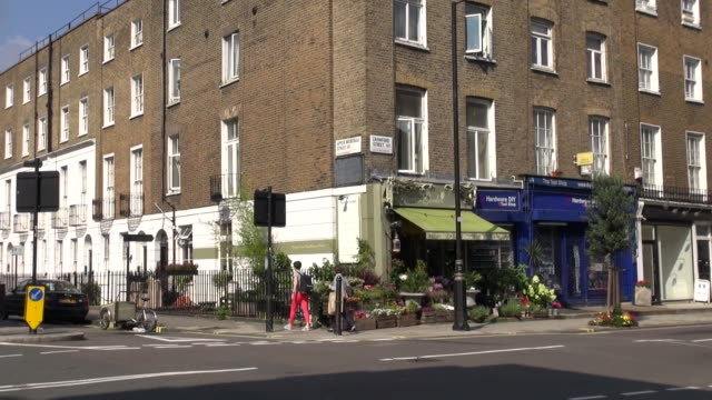 sequence of shots of flower shop in street just off baker street in central london england with man and woman chatting and woman crossing the road - メリルボーン点の映像素材/bロール