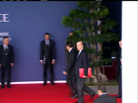 sequence of shots of french president nicolas sarkozy arrival at g-20 summit. walks past the world flags and past the sign that says g20 france 2011... - president of france stock videos & royalty-free footage