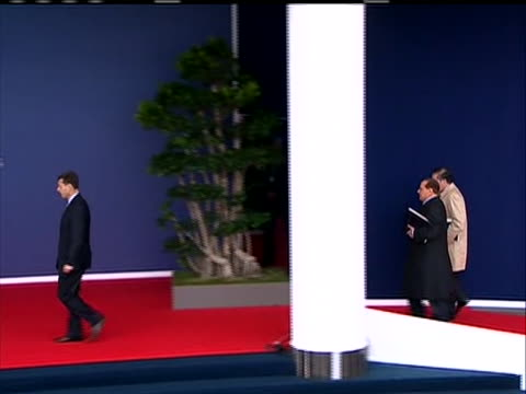 a sequence of shots of prime minister of italy silvio berlusconi arrival at g20 summit cu gets out of the car walks past the world flags waves and ws... - (war or terrorism or election or government or illness or news event or speech or politics or politician or conflict or military or extreme weather or business or economy) and not usa video stock e b–roll