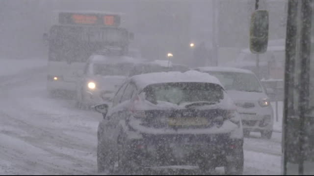 vídeos de stock, filmes e b-roll de sequence of shots showing vehicles on the road during a snow blizzard in tunbridge uk - chuva congelada