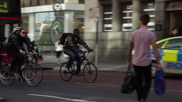 Sequence of tracking shots showing people riding bicycles on a busy road near Liverpool Street Station on a sunny day in London, UK.