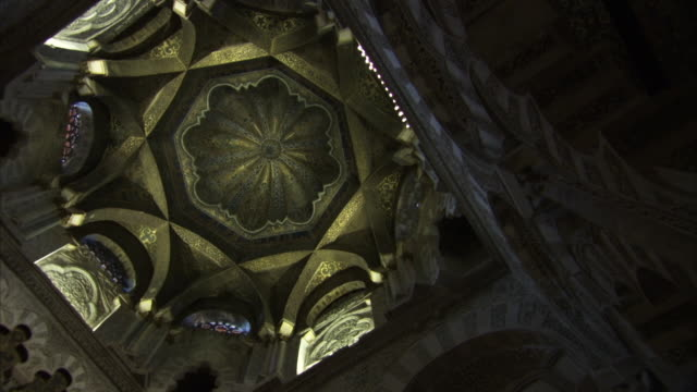 Sequence of twisting wide shots showing the ceiling of the Mosque–Cathedral (Mezquita) of Córdoba, Spain.