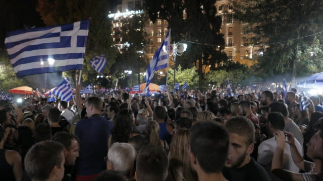 vidéos et rushes de sequence of two wide shots and one panning shot showing supporters of 'oxi' celebrating on the night that the referendum results over bailout terms... - athens greece