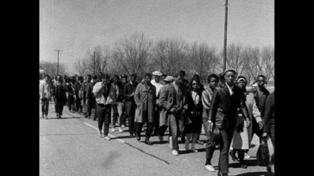 "stockvideo's en b-roll-footage met sequence of wide shots showing a group of protest marchers marching along the highway from selma to montgomery, singing ""keep your eyes on the... - 1965"