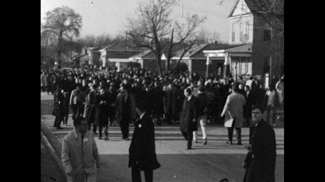sequence of wide shots showing protest marchers walking past brown chapel in selma towards the courthouse to register to vote 15th march 1965 - 1965 selma marches stock videos & royalty-free footage