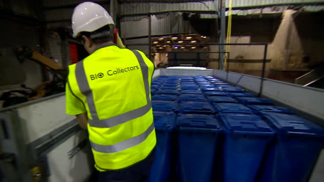 Sequence of worker removing wheelie bin from flatbed truck and close up of food waste in bin