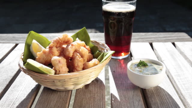 sequence panning across a basket of scampi and a pint of beer on a wooden table. - unhealthy eating stock videos & royalty-free footage
