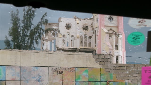 POV sequence shot from a car showing a central area of Port-au-Prince devastated by the 2010 earthquake, including the Cathédrale Notre-Dame de L'Assomption, Haiti (footage shot approximately four years after the earthquake).