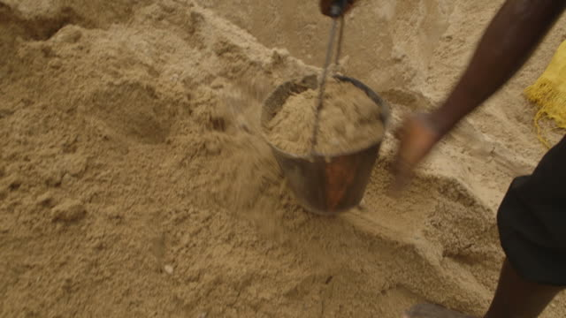 sequence showing a bucket of sand being poured into a pan at a diamond mine in sierra leone. - sierra leone stock videos & royalty-free footage