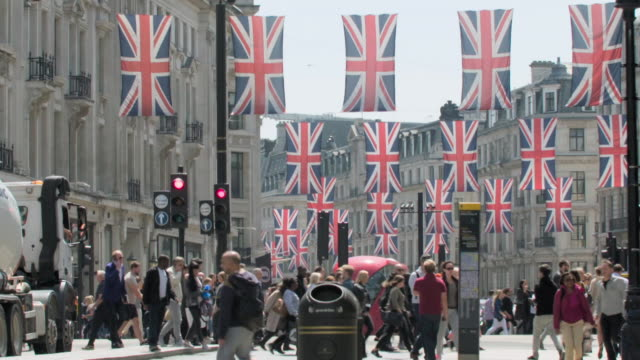 Sequence showing a busy Regent Street with Union Jack banners, London, UK.