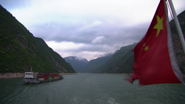 sequence showing a chinese flag flying from the stern of a ship as it sails along the yangtze river.  - chinese flag stock videos and b-roll footage
