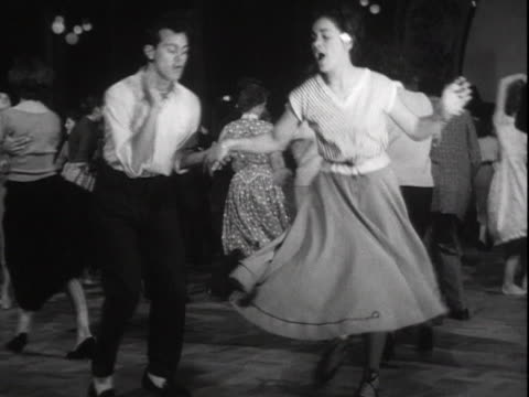 vidéos et rushes de sequence showing a couple dancing to rock and roll music in a dance hall. - rock