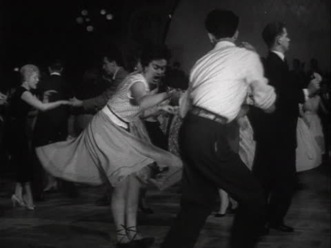 stockvideo's en b-roll-footage met sequence showing a couple dancing to rock and roll music in a dance hall - 1956