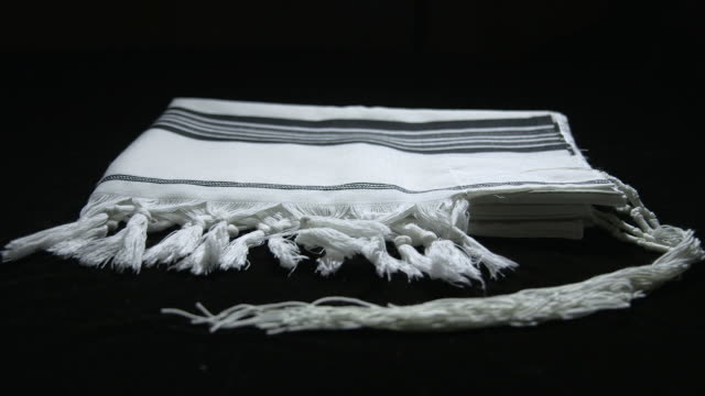 Sequence showing a folded tallit (Jewish prayer shawl) on a black studio background.