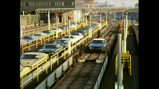 sequence showing a ford mustang being driven off the assembly line in detroit to join a queue of other mustangs in a large parking lot full of cars;... - 1972年点の映像素材/bロール
