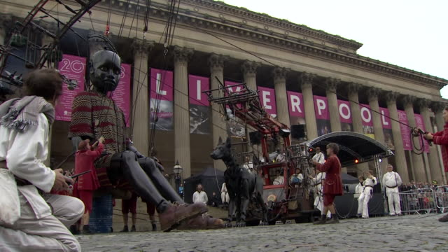 Sequence showing a giant human puppet walking through the streets of Liverpool