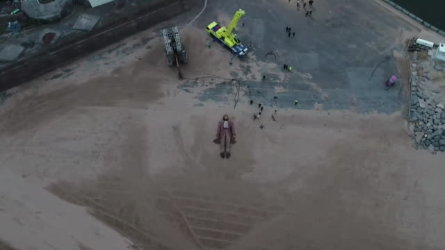 Sequence showing a giant human puppet walking through the Wirral