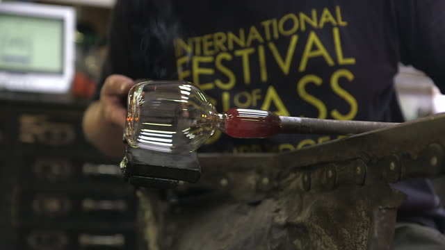 vidéos et rushes de sequence showing a glassblower shaping a small glass bottle attached to a blowpipe, uk. - artisanat