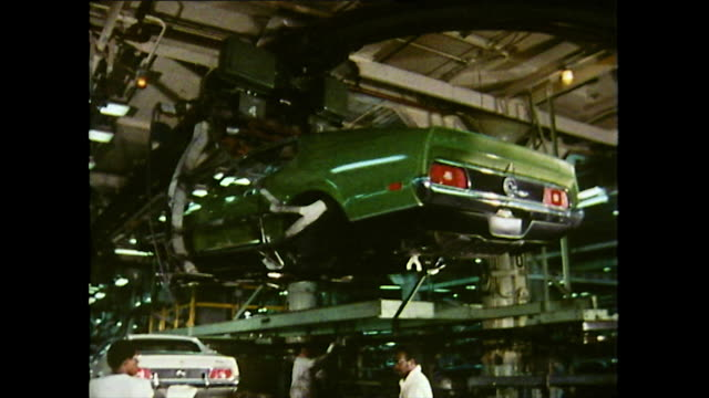 vídeos de stock e filmes b-roll de sequence showing a green ford mustang is carried by a mechanical hoist and lowered onto the production line by male workers at the ford river rouge... - chassi
