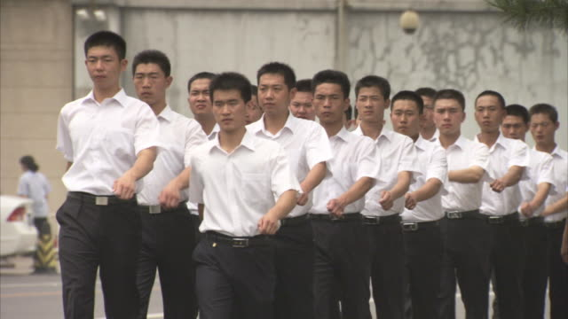 Sequence showing a group of young men wearing uniform marching in Beijing, China.