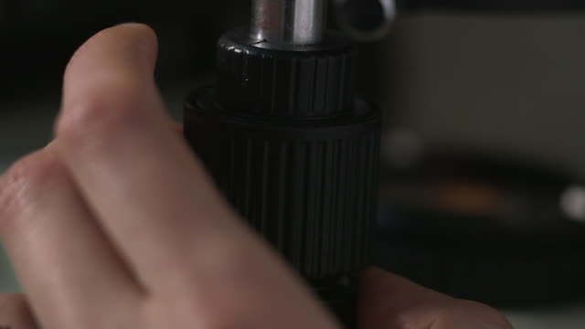 sequence showing a hand turning a focus knob on a microscope, uk. - knob stock videos and b-roll footage