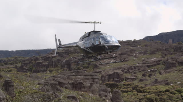 Sequence showing a helicopter landing on top of a Tipui mountain, Venezuela.