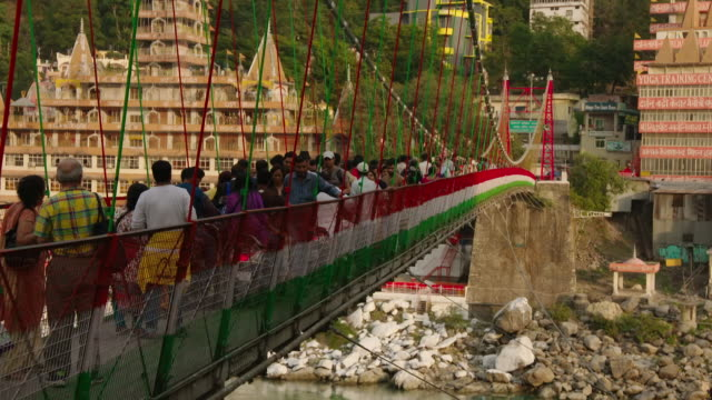 Sequence showing a high, busy footbridge being crossed by pedestrians, cattle and motorbikes and painted in national colours above the Ganges in Rishikesh, Uttarakhand, India.