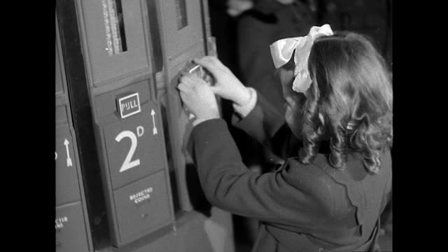 sequence showing a little girl purchasing a chocolate bar from a dispensing machine - bbc archive stock-videos und b-roll-filmmaterial