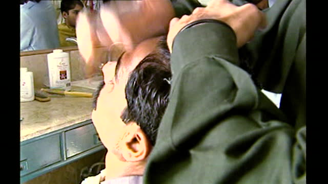 sequence showing a man getting a wet shave at a barber's shop in islamabad; 14th september, 2001. hand with rings shaves beard with razor. reflection... - body care stock videos & royalty-free footage