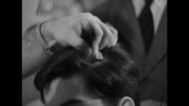 Sequence showing a man having his hair permed by a barber