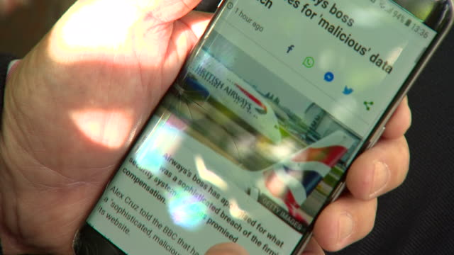 sequence showing a man looking at the british airways website on a smartphone - web page stock videos & royalty-free footage