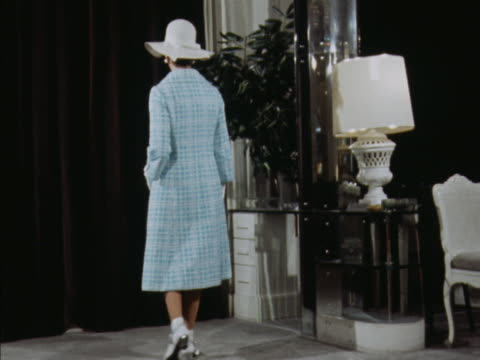 stockvideo's en b-roll-footage met sequence showing a model wearing a matching blue patterned coat and dress with white ankle boots designed by norman hartnell - designerkleding