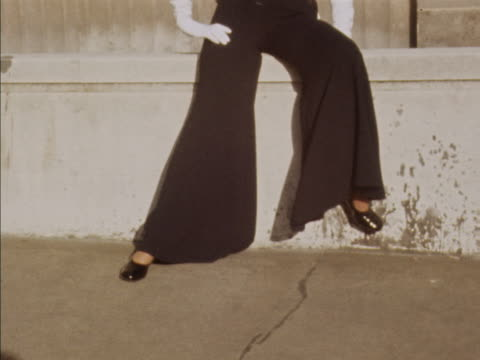 sequence showing a model wearing a sleeveless black trouser suit with polka dot scarf designed by lachasse - polka dot stock videos and b-roll footage