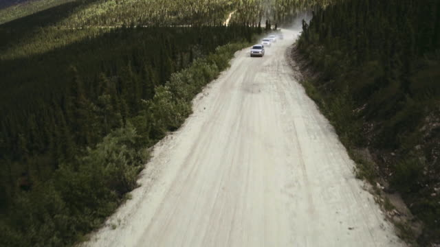 Sequence showing a motorcade of large cars travelling through the Klondike, Yukon Territory, Canada.