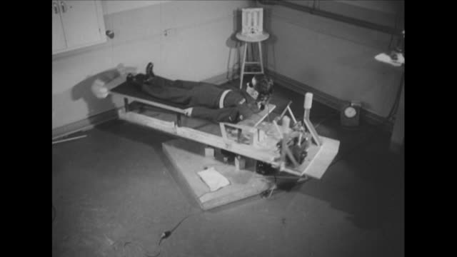 sequence showing a pilot laying on a revolving table during air sickness training - aeroplane ticket stock videos & royalty-free footage