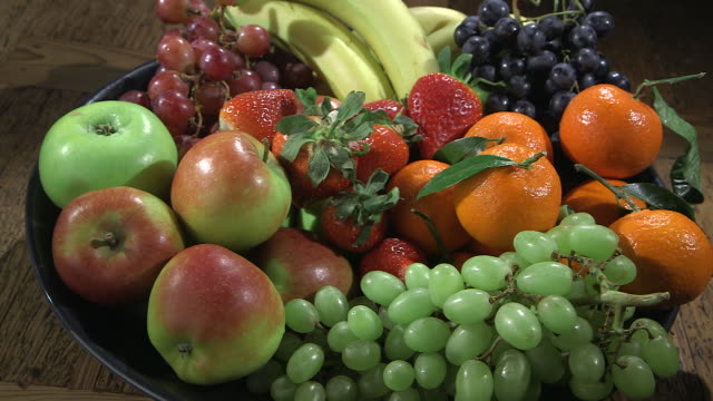 vidéos et rushes de sequence showing a plentiful fruit bowl filled with popular fruits. - coupe à fruits