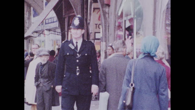 sequence showing a policeman in uniform walking along busy streets amongst the community in brixton, london; 1973. - capital cities stock videos & royalty-free footage