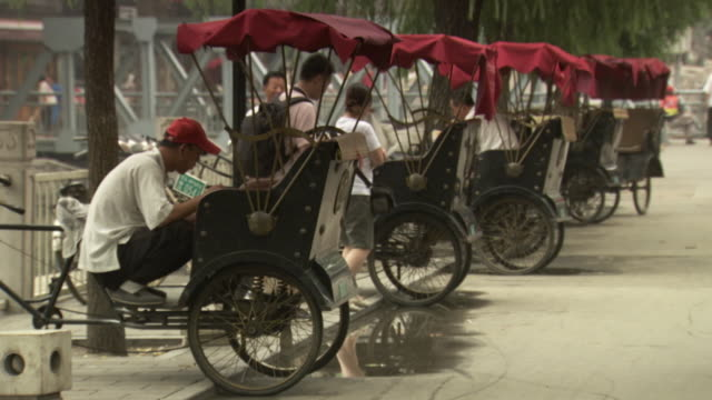 vidéos et rushes de sequence showing a rickshaw driver eating his lunch in beijing, china. - pousse pousse