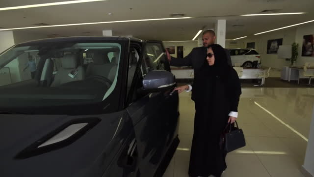 sequence showing a saudi women looking at a land rover in a car showroom in riyadh saudi arabia - censura video stock e b–roll