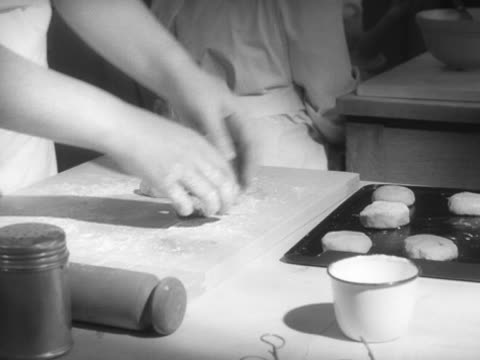 stockvideo's en b-roll-footage met sequence showing a school girl placing hot cross buns onto a baking tray during a cookery lesson - huishuidkunde