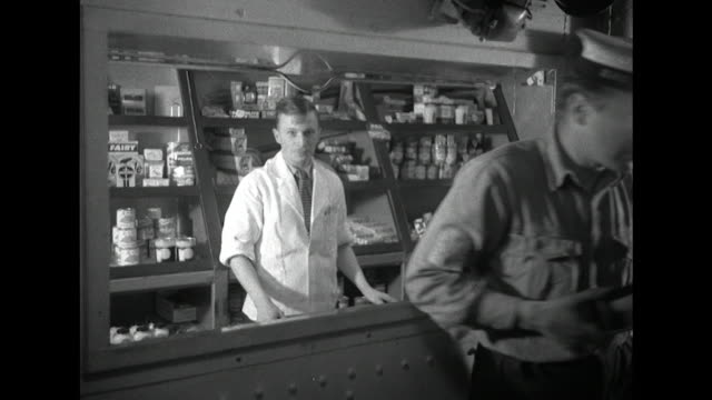sequence showing a shop, barbers and launderette onboard a uk aircraft carrier. - waschsalon stock-videos und b-roll-filmmaterial