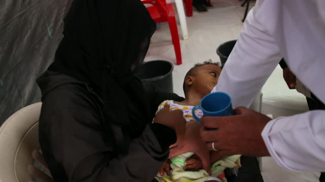 sequence showing a sick child treated for cholera in a hospital in sanaa, yemen - traditional clothing stock videos & royalty-free footage
