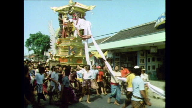 sequence showing a traditional balinese funeral procession in 1985 three women being carried in chairs cut tall brightly coloured wagghu tower being... - pacific islander stock videos & royalty-free footage