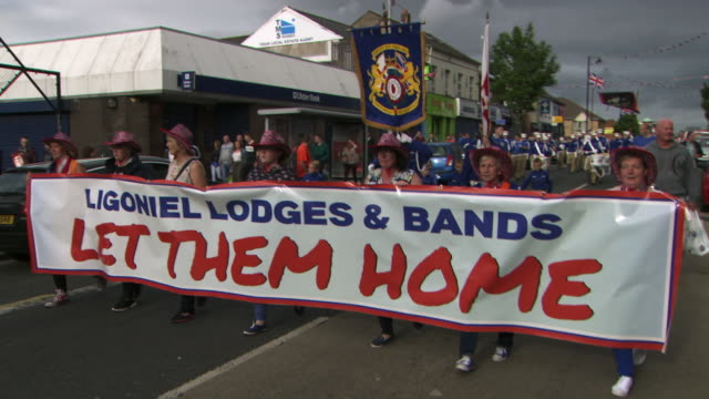 sequence showing a unionist/loyalist march towards a predominantly catholic area that has been blockaded by the police, belfast, northern ireland. - marching stock videos and b-roll footage