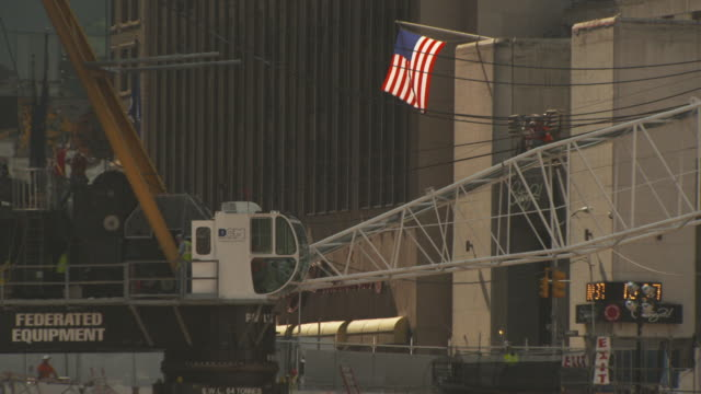 stockvideo's en b-roll-footage met sequence showing a united states flag by a large construction site for the new world trade center buildings and memorial to the attacks of september 11th 2001 during the summer of 2011, manhattan, new york city, usa. - aanslagen op 11 september 2001