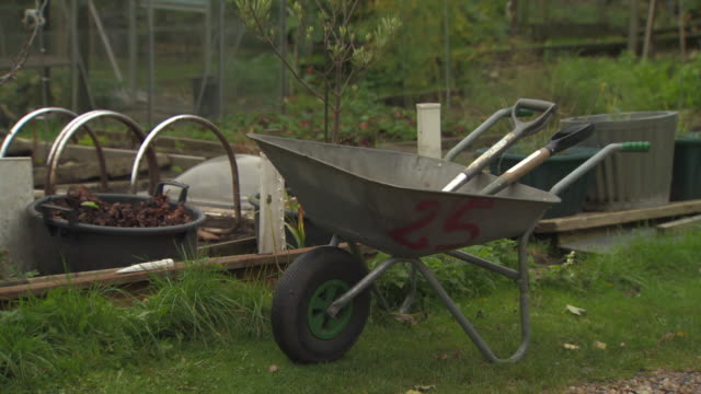 sequence showing a wheelbarrow containing garden tools and a greenhouse potting shed at an urban allotment, uk. - wheelbarrow stock videos and b-roll footage
