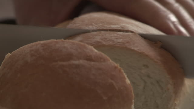 sequence showing a white loaf being cut into slices with a knife. - loaf of bread stock videos & royalty-free footage