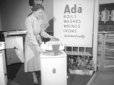 stockvideo's en b-roll-footage met sequence showing a woman demonstrating a new washing machine at the ideal home exhibition. - tentoonstelling