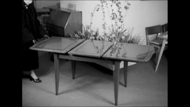 sequence showing a woman demonstrating an extendable table at the earls court furniture exhibition - earls court stock videos & royalty-free footage