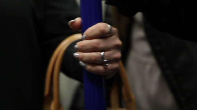 sequence showing a woman with painted nails and a handbag gripping a blue pole on an underground train, london, uk. - stange stock-videos und b-roll-filmmaterial